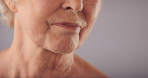 Senior female face with wrinkled skin on face and neck