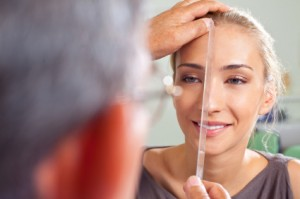 woman's face being measured by plastic surgeon