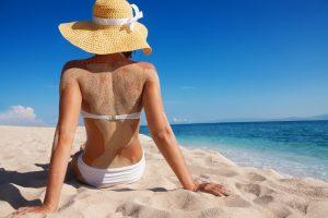 beautiful woman relaxing on sandy beach alone