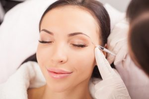 Attractive healthy woman is getting botox injection and smiling.