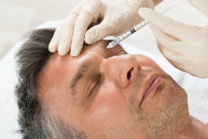 Man Receiving Cosmetic Injection With Syringe