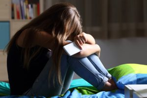 teen girl depressed with cell phone
