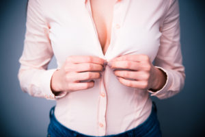 woman's cleavage while buttoning her shirt