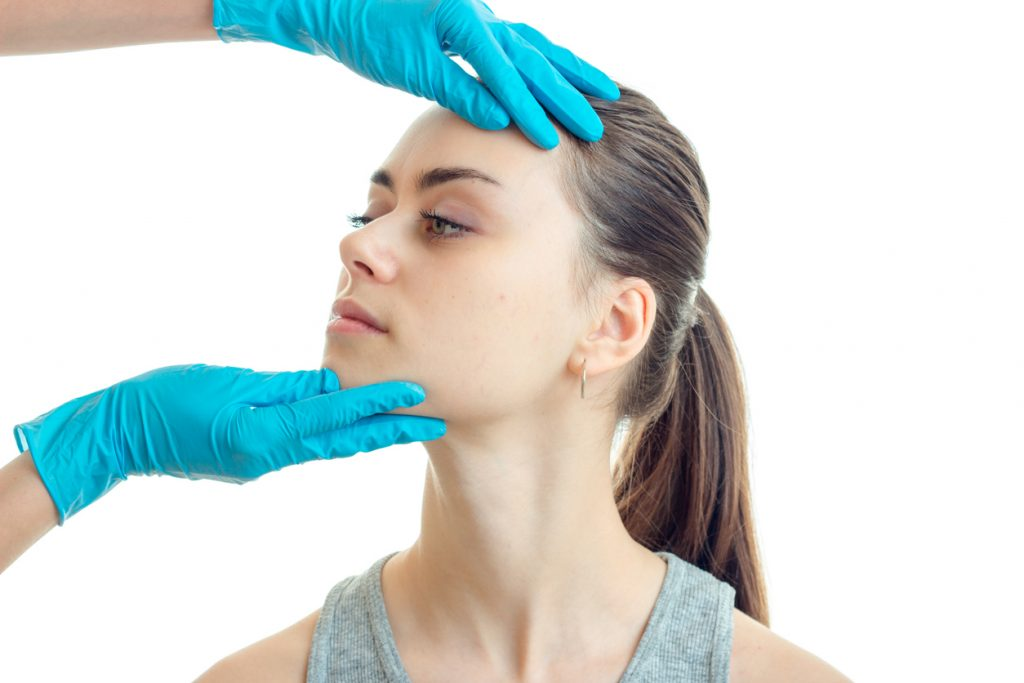young woman having revision rhinoplasty consultation
